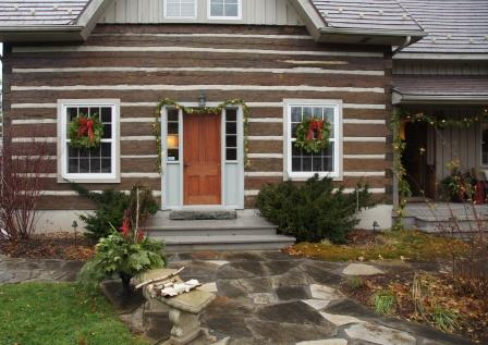 Little is needed to enhance the rustic beauty of a log house. A few added greens add to the bushes growing by the door.
