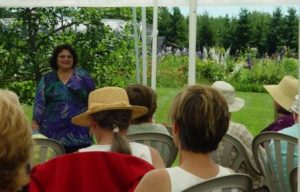 Christine discusses delphs with nursery beds in the background.