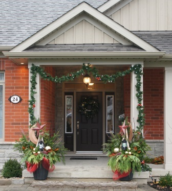 A garland frames the front porch while pots of greenery and sparkle balance the entrance.