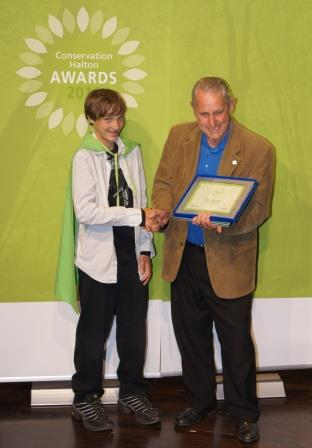 """Hayden Downes-Mills, wrapped in a """"Conservation Hero"""" cape, being congratulated by Milton mayor Gord Krantz."""